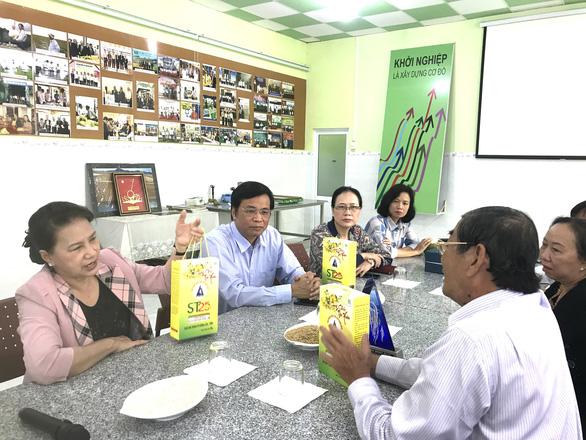 Ông Hồ Quang Cua (bìa phải) giới thiệu gạo thơm ST25 với Chủ tịch Quốc hội Nguyễn Thị Kim Ngân